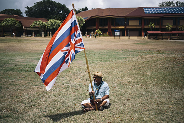 HONOLULU, HAWAII - APRIL 13:  A protestor sits on the Great Lawn with a Hawaiian Flag during a protest of the Thirty Meter Telescope in front of the Great Lawn at Kapiolani Community College on April 13, 2015 in Honolulu, Hawaii.