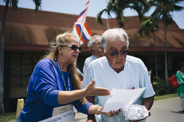 HONOLULU, HAWAII - APRIL 13:  KCC STEM Center Coordinator Keolani Noa goes over a fact sheet listing facts about TMT and Mauna Kea during a protest of the Thirty Meter Telescope in front of the Great Lawn at Kapiolani Community College on April 13, 2015 in Honolulu, Hawaii.